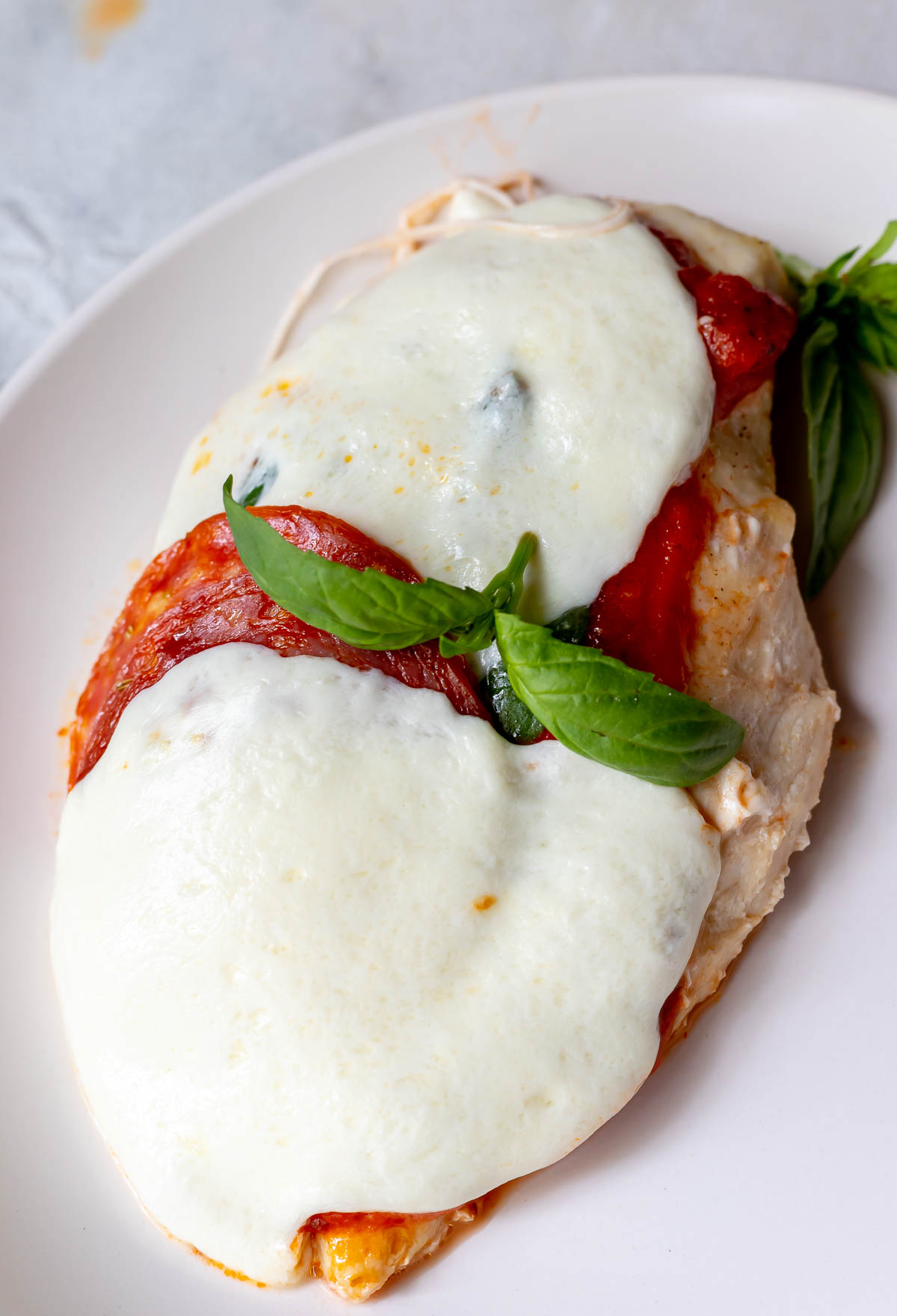 pizza chicken breast smothered with mozzarella and pepperoni, topped with basil leaves
